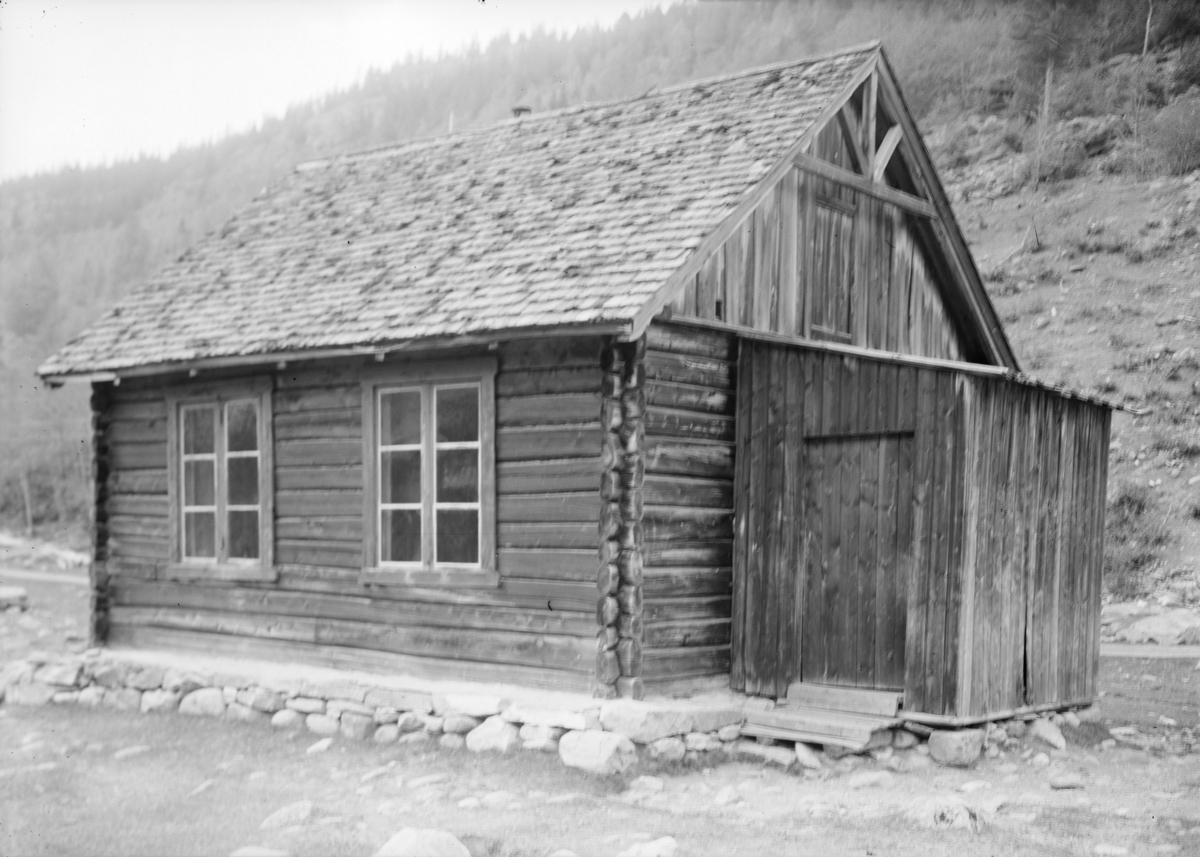 Lite tømmerhus med påbygd inngang