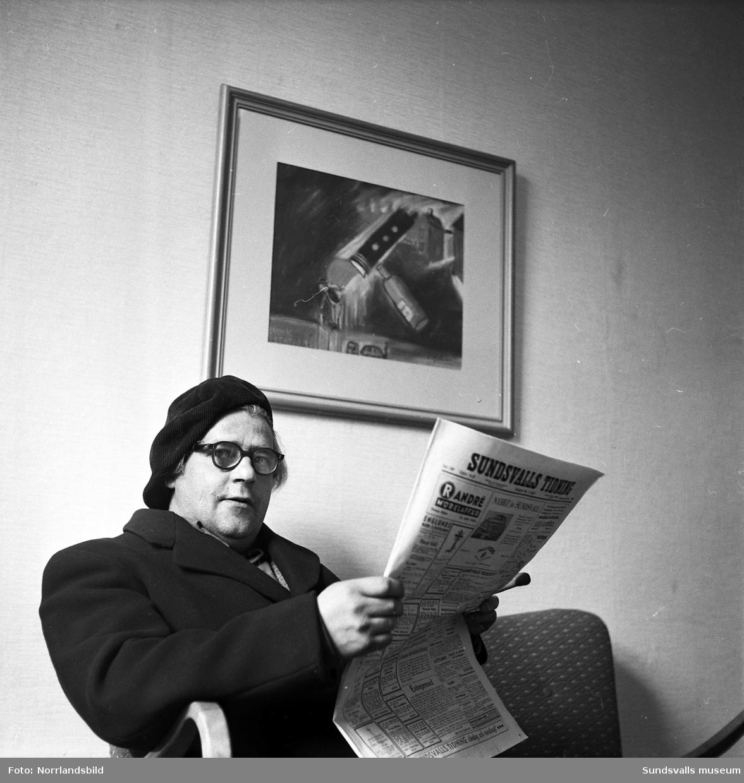 Konstnären Ture Åslin med basker och överrock, sitter och läset Sundsvalls tidning.