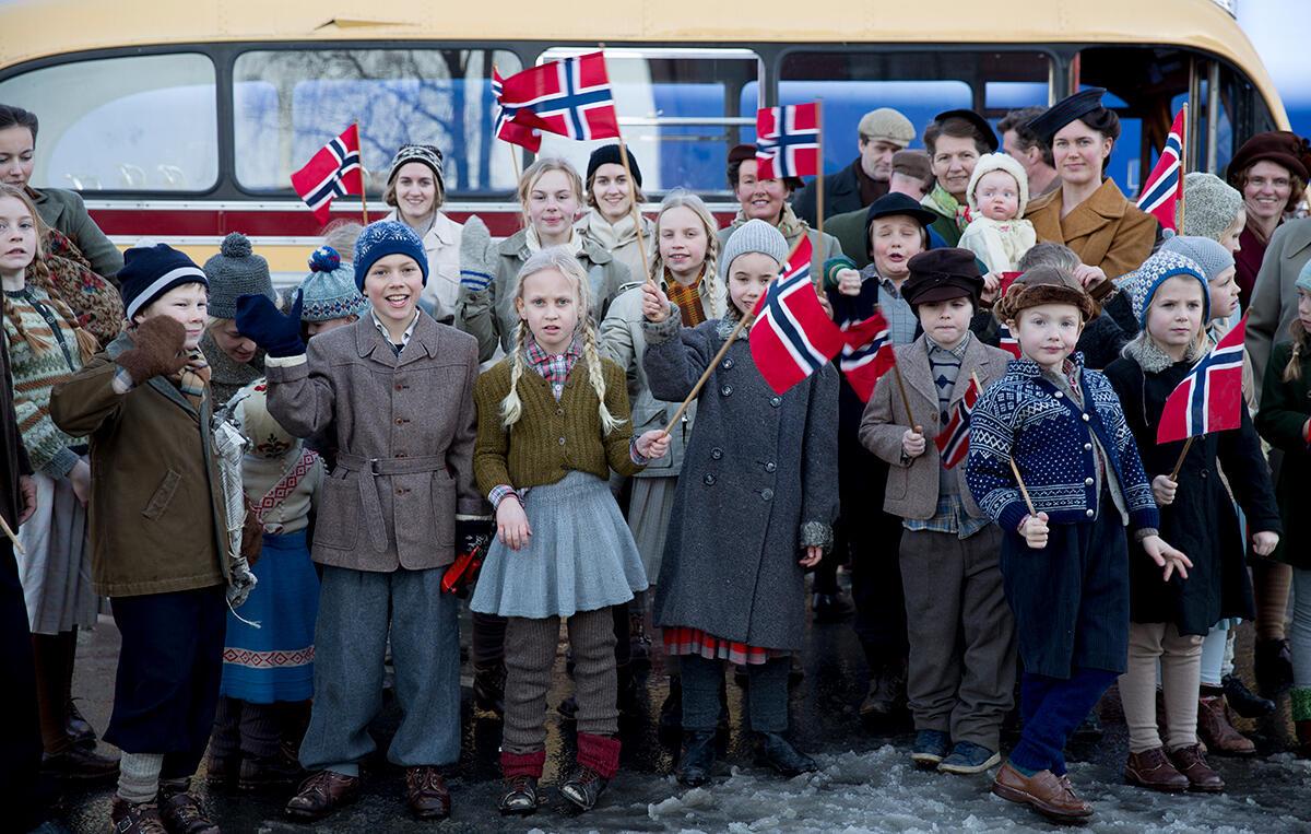 Langs jernbanesporet blir kongens tog hyllet med norske flagg. Alvoret har ikke gått opp for folk. Foto: Tine Poppe/Paradox.