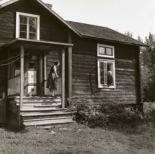 Ett hus med förstukvist och bemålade dörrar. På förstukvisten står en kvinna och tittar mot en man som sitter i ett fönster.