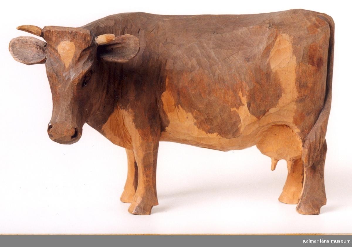 KLM 39255:9. Skulptur, av trä, bemålad. Ko med huvud vridet mot vänster. Sidgnerad, H.C. Inristat på kossans högra bakdel. H.C. = Helge carlsson.