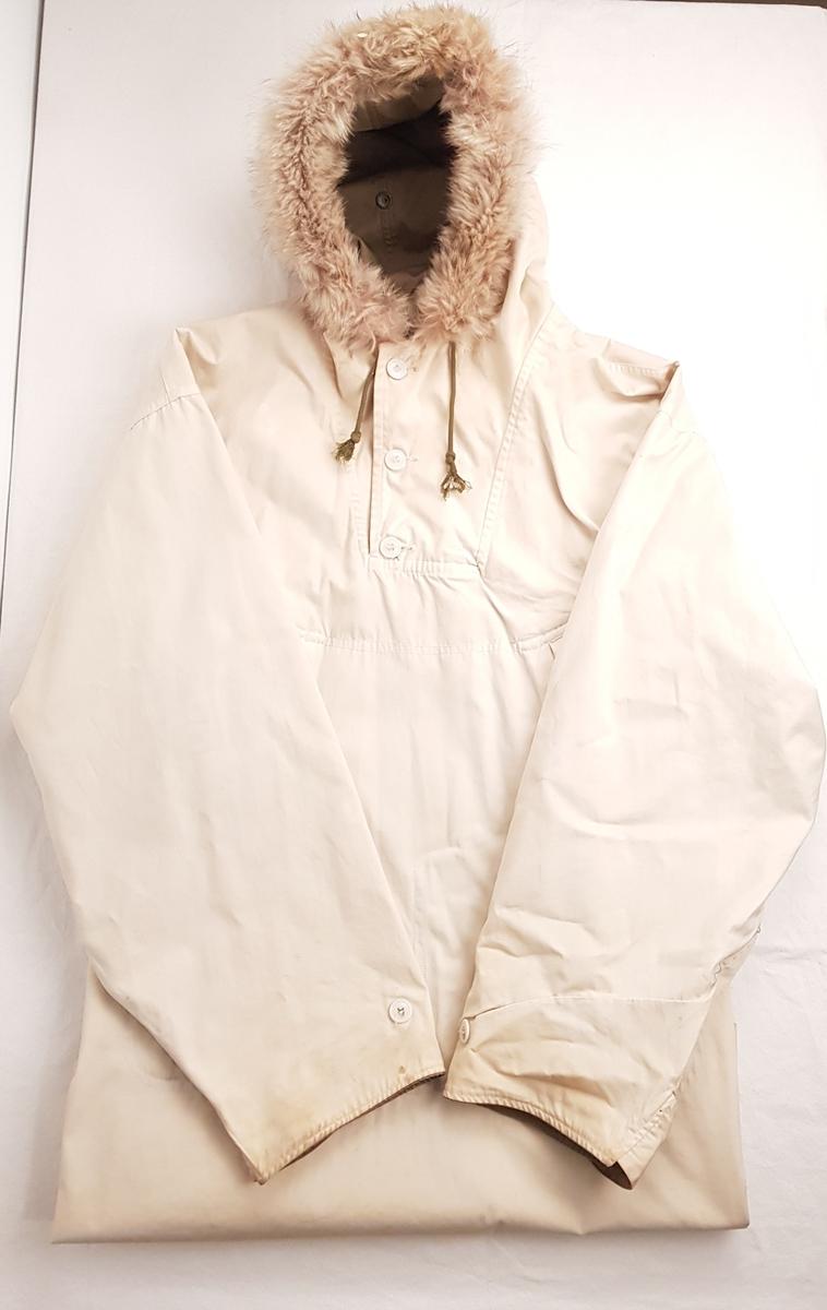 Anorakk for vinterbruk med en hvit og en grønn side. Hetten har pelskant og løpegang med grønn snor.