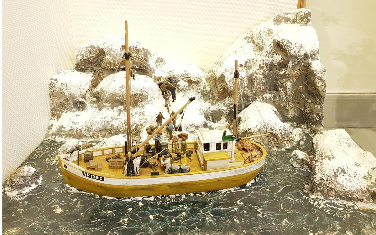 """Modell i gips og tre av Håkon Furnes sin båt """"Sleipner"""" montert med landskap og mennesker om bord i båten."""