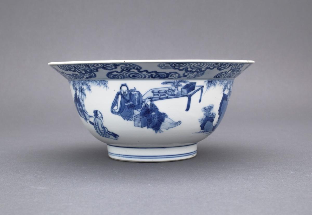 """Bolle med utbrettet kant. Figurmotiver på utsiden av cavetto. Figurene er organisert i flere ulike grupper. Også et figurmotiv i speilet på bollen. På undersiden av kanten finner vi skyer. På oversiden av kanten et prunusmotiv. Motivet kan være """"De syv vise menn i bambuslunden"""" med en representasjon av Li Bai i speilet."""