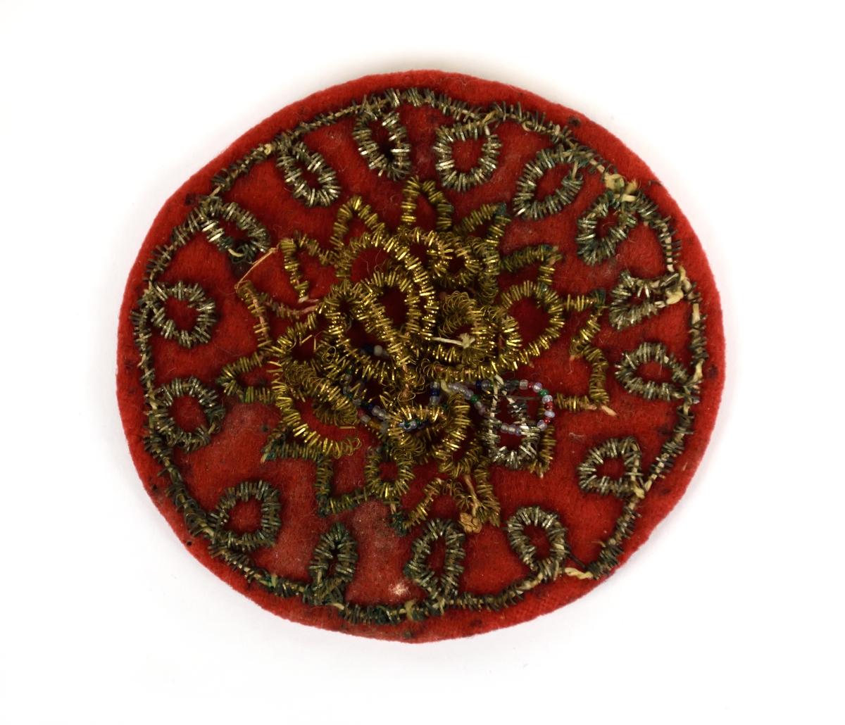 Hårsmycke av röd vadmal broderat med metalltråd, spunnen på lingarn. Till hårsmycket hör ett pannband broderat med vita pärldekorationer samt hängande tennplåtar i grupper.