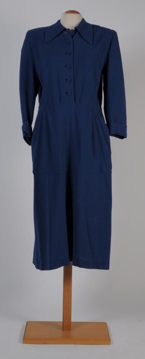 Klänning av ylle-georgette i mellanblå färg. Plagget är avskuret i midjan, knäpps med tygöverklädda knappar, krage samt trekvartslånga ärmar med uppslag.