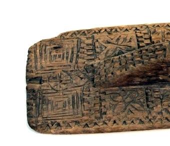 Mangelbräde av tunn plan skiva med avrundade hörn. Handtaget är skuret i ett stycke med brädet och vid handtagets främre del sitter två primitivt formade människoansikten. Brädets hela yta är täckt av inskurna, enkla geometriska ornament.