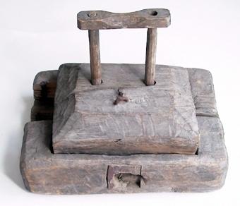 Råttfälla av trä med fyrkantig bottenplatta i vilken har borrats två hål. Mellan hålen har monterats ett trästycke, som i nedslaget läge fungerar som råttdödare.