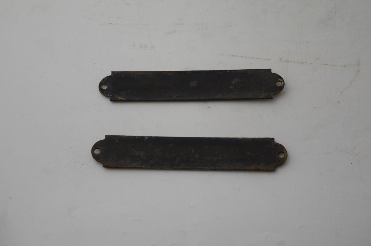 Rektangulære skilt med hvit bakgrunn, sort skrift og sort ramme. Emaljert metall. Sort bakside. Skilt brukt i jernbanevogner.