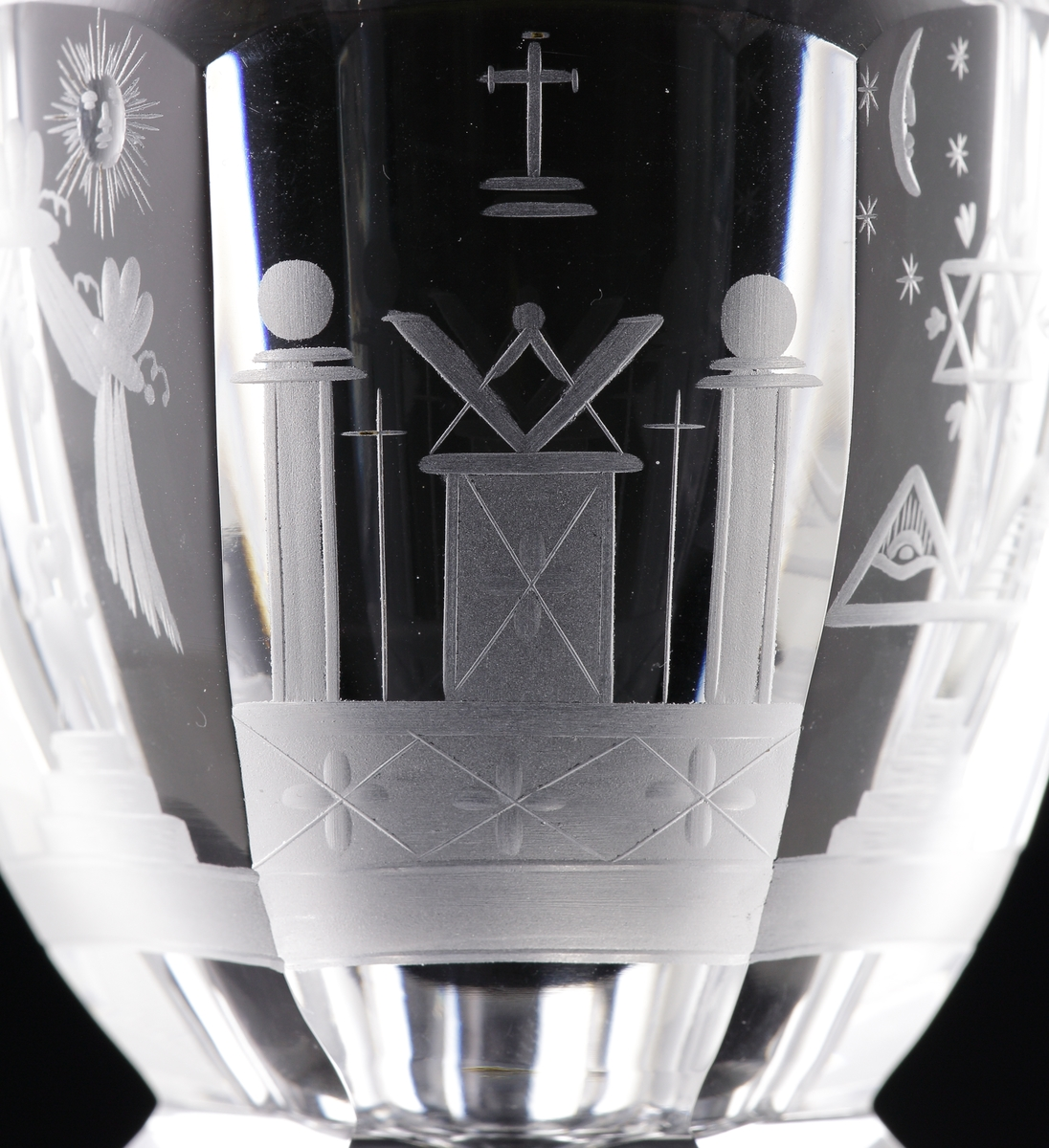 Vinglas.  Kupa, ben och fot är facettslipade. Graverad dekor av frimurarsymboler på kupan.