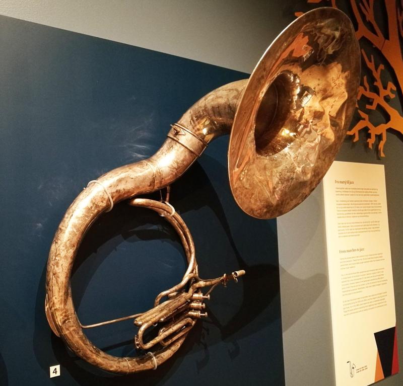 Tubaen er ferdig behandlet og henger på veggen i utstillingen Virvel og fanfare, like velbrukt og bulkete som da den ble spilt på.