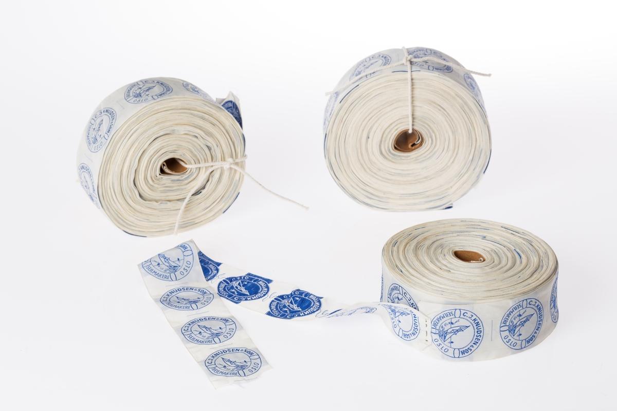Tre ruller med merkebånd fra materialprodusent. Sirkelformet merke med tekst og motiv av en seilbåt.