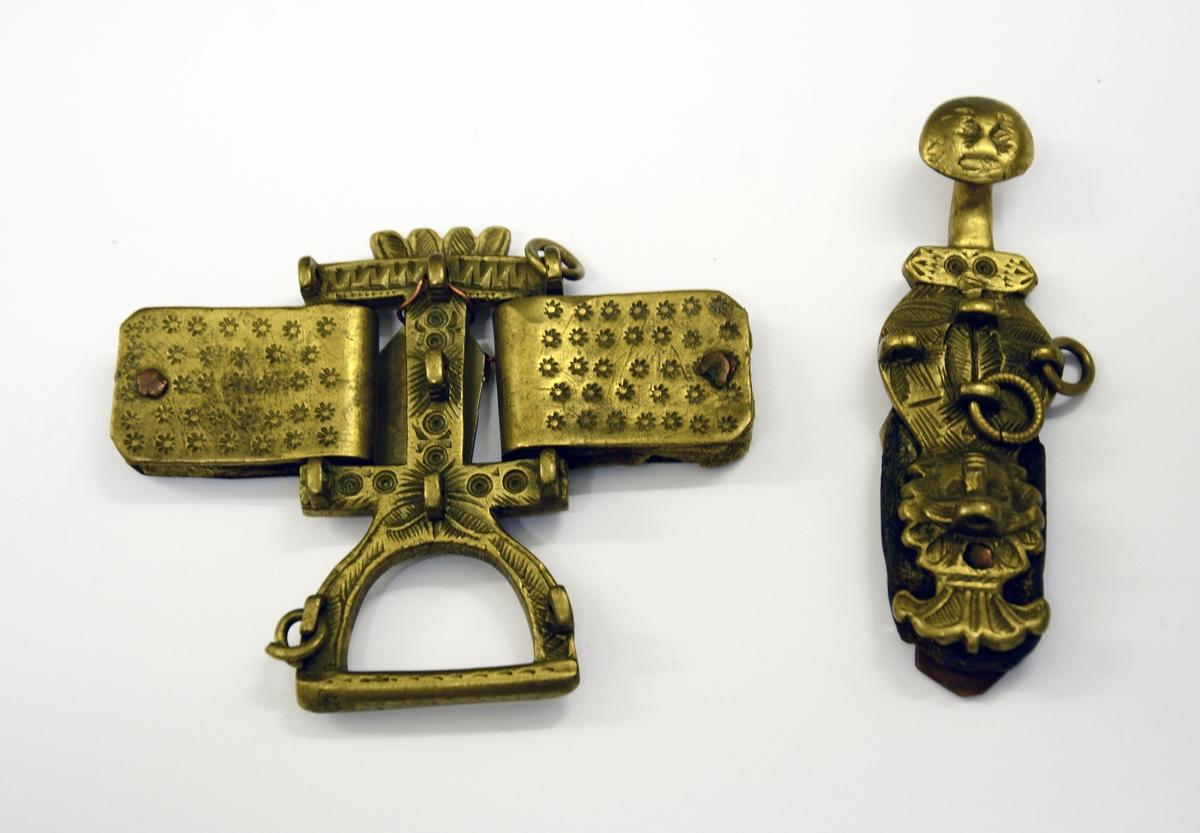 Slirehempe til belte og beltelås i messing. Fra protokollen: Bæltebeslag for tollekniver, av messing. Selve beslaget bestaar av a) 1 sprote (stolpelås eller beltelås) med paasatte 4-5 ringer og ornamenter i form av to masker. b) En stolpe (slirehempe) med løkke paa. Fra stolpen gaar 2 par tvertagger, som gir plads til rembeslagene. Disse, der bestaar av 2 dobbeltbiøede plater ornerte med stjernepunkter, gaar rundt mellem tvertaggerne, og omslutter skindremmen som bokpermer. Beslaget har ringe og ornamenter.