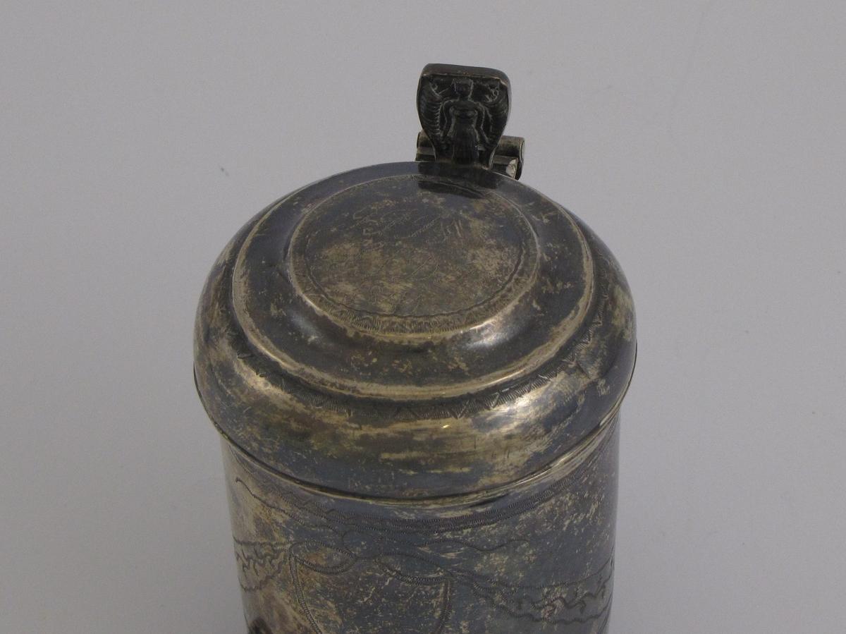 Sølvkanne med lokk i drevet sølv. Drammekanne med gravert dekor. På lokket er gravert inn F (?) T (?)  B - S S D B 1841