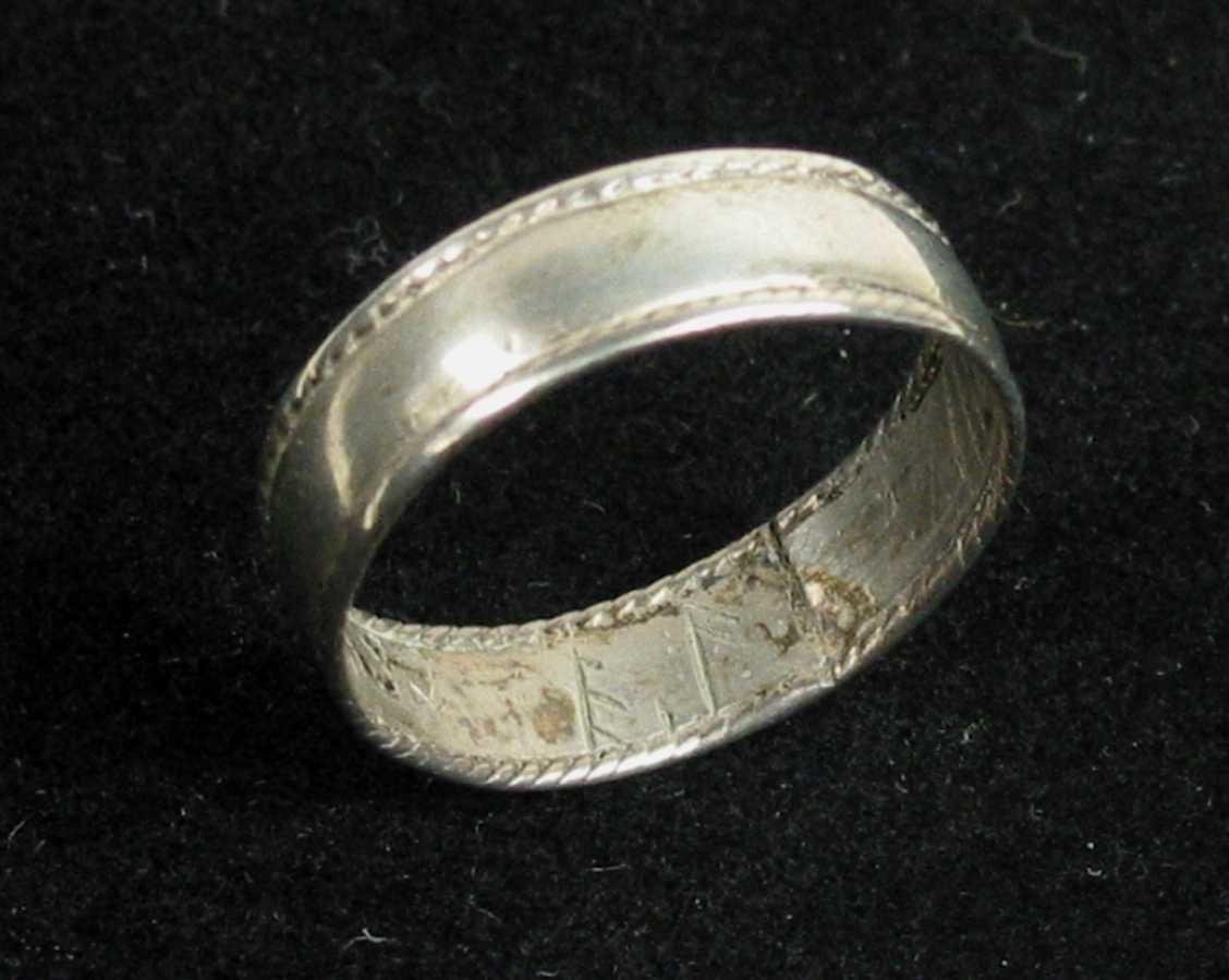 Fingerring av bredt flatt sølvbånd med tvinnetrådsgjord langs begge kantene. Ellers er den glatt.
