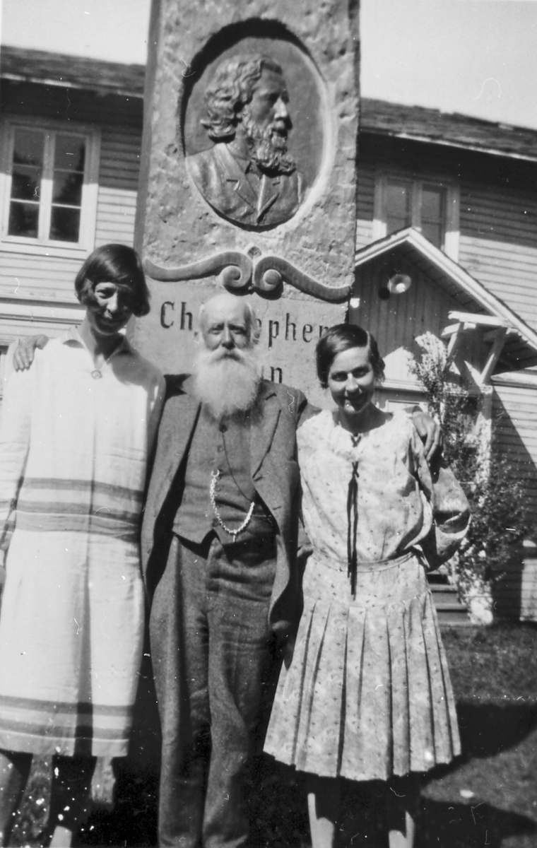 I. M. Egnund og to damer foran statuen av Christopher......