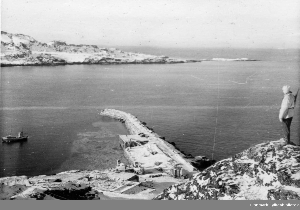 """En soldat fra 2.Bergkompani står vakt på en høyde over snedekket landskap. I bakgrunnen ser man en branntomt, en lang molo og en fiskebåt. Et par fiskebåter ligger på land.   Bildeserien """"Frigjøringen av Finnmark 1944-45"""" viser et unikt materiale fotografert av soldater i Den Norske Brigade, 2. Bergkompani under deres oppdrag """"Frigjøringen av Finnmark"""" som kom i stand under dekknavn """"Øvelse Crofter"""". Fakta rundt dette bildematerialet illustrerer iflg. vår informant, George Bratli: """"2.Bergkompani, tilhørende Den Norske Brigade i Skottland,  reiste fra Skottland 30. oktober 1944 med krysseren «Berwick» til Scapa Flow på Orkenøyene for å slutte seg til en større konvoi som skulle være med til Norge. Om bord på andre skip var det mange russiske krigsfanger som hadde vært på tysk side og som nå ble sendt hjem.  2.Bergkompani forlot havn 1.november 1944 og kom til Murmansk, Sovjetunionen, 6. november 1944.  De ble her lastet om og fraktet til Petsamo, Sovjetunionen, hvor de ankommer 11.november 1944.  Kompaniet reiser så til Sandnes utenfor Kirkenes og blir forlagt der frem til 26.november 1944. De flytter så videre til Skipparggura.  Den 29.november reiser deler an kompaniet til Rustefielbma og Smalfjord og noen drar opp på Ifjordfjellet.   17. desember ankommer resten av kompaniet til Smalfjord. 30.desember blir en avdeling sendt til Hopseide og 8. januar 1945 blir noen sendt til Kunes. Den 14. januar er kompaniet delt og ligger i Kunes, Kjæs, Børselv, Hopseide og Smalfjord. 5. februar 1945 blir 3.tropp sendt over Porsangerfjorden for å operere i Olderfjorden. Her var de i kamp og hadde tap i  Billefjord og Sortvik. 8.mars 1945 kom noen til Renøy og 12. mars kom første del av kompaniet til Brennelv. 7.mai begynte kompaniet å bygge ny kai i Hambukt. 19. mai ble de som hadde falt begravd i Lakselv. 8. juni ble kompaniet flyttet fra Brennelv til Tromsø for så å bli sendt videre til Mo I Rana 16.juni."""""""