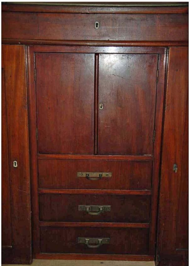Anmärkningar: Skrivbord med pulpet, omkring 1900.  Gångjärnsförsedd snedklaff som fungerar som skrivunderlag. Längst ned på klaffen finns en mässingslist som hindrar pappret från att åka ned. På sidorna om klaffen finns vardera 3 stycken draglådor med svarvade knoppar. Fronten är försedd med en nyckelskylt av ben. På flankerna av fronten finns vardera en draglåda med svarvade knoppar. Nederdelen består av två spegelförsedda skåp. I dessa finns vardera 5 stycken lådor med dragringar av mässing. Mellan skåpen finns en byrådel med 3 stycken draglådor med mässingshandtag samt en lucka med dubbla dörrar.  Bild 10485__b visar möbeln när dörrarna och klaffen är öppnade. Möblen består av 4 delar. Pulpeten, skåpen och byrådelen mellan dessa går att ta isär. Hela möblen är fanerad med mahogny, utom nederdelens spegelförsedda dörrar, speglarna är av massiv mahogny.  Tillstånd: Två dragknoppar saknas på överdelen. Två lås och en nyckelskylt av järn är lösa och ligger i den högra frontlådan.  Historik: Gåva från fröken Olga Andersson. Enligt en äldre registrering har möbeln tillhört Rudolf Gagge.  Negativnummer X-1954