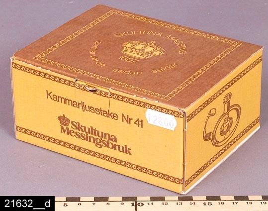 """Anmärkningar: Kammarljusstake, 1983.  Rund ljusstake med profilerad ljushållare och skålformad fot. Öppet handtag med stämplar i form av en krona och texten """"SKULTUNA 1607"""" (bild 21632__b). Undertill är ljusstaken märkt """"No 41 SKULTUNA 1607 I10"""" (bild 21632__c), beteckningen I 10 betyder att föremålet är tillverkat 1983. Originalförpackningen finns bevarad (bild 21632__d). Det är osäkert när modellen började att tillverkas. År 2007 var den fortfarande i produktion. Enligt en broschyr, utgiven av museet 2007 och benämnd """"Skultunastämplar 1800-2000"""", började den typ av stämpel som finns på föremålet användas 1922. Den användes fortfarande år 2007. H:70 D:115 Br:145 (avser diametern samt handtaget)  Tillstånd: Nyskick.  Historik: Inköpt för 75 kronor + moms 1983."""