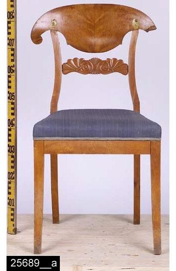 """Anmärkningar: Stol, Karl Johan, omkring 1820.  Peltaformat överstycke. S-svängda bakstolpar (bild 25689__b). Genombruten rygg och en ryggslå med skuren dekor i form av ymnighetshorn. Stoppad sits med blått tygöverdrag. Samtliga ben är utåtsvängda från stolen (bild 25689__b). H:865 Br:495 Dj:490  Hela stolen är fanerad med mahogny, blindträet är furu.  Invnr. 25689 ingick ursprungligen i invnr. 10053 som bestod av sex poster. Invnr. 10053 har splittrats av projekten Sesam och Access. Se även invnr. 10053, 25688-25690, 28531 och 28532.  Tillstånd: Överstycket är skadat på höger sida. Fanerskador på överstycket som fyllts igen med gul-guld aktig färg.  Historik: Enligt liggaren """"Inköpt av en jude"""", Sala."""