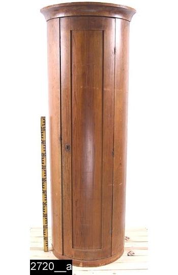 Anmärkningar: Hörnskåp, s.k. kolonnskåp, benämning efter formen, rundat, möjligen empire, 1800-t.  Framskjutande rundat krön. Spegelförsedd dörr med nyckelskylt i järn. Invändigt ett hyllplan med skruv i järn undertill (2720__b). Spår av ytterligare två hyllplan. Invändigt femtiotvå krokar av mässing (senare) med målade nummer nedtill, elva av krokarna sitter på dörren. Invändigt ett lås i järn. H:1885 Br:690 Dj:530  Skåpet är betsat. Hyllplanet är ursprungligt, krokarna. är senare.  Tillstånd: En svärtad sockel är märkt med inv. nr. 26332 (bild 26332__d) och skall, enligt sesamprojektet, sitta överst på ett kolonnskåp med samma nummer. Den passar dock ej på detta skåp. Möjligen hör den samman med inv. nr. 2720 där den passar som sockel (ej överdel).  Historik: Köpt av fru Ida Nygren, Västerås, Kr. 30:-. Skåpet har en gång använts som nyckelskåp på Vallby Friluftsmuseum.