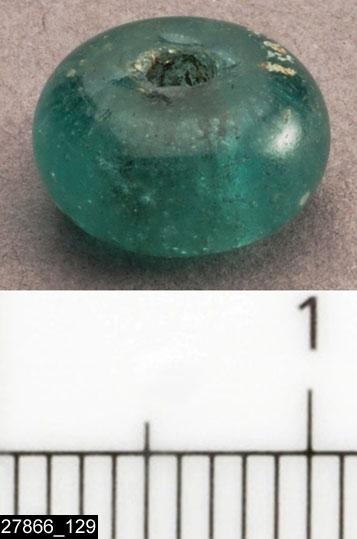 Anmärkningar: Badelunda sn, Tuna undersökt 1952-1953 Pärla, från båtgrav daterad till yngre järnålder, 850 e.Kr. (Vikingatid)  Pärla av glas, från grav 75 (fyndnr 129). 1 st, klar, grön. Diam ca 8 mm Utställd Forntid 2014  Den ursprungliga ordningen på pärlorna, enligt tidigare registrering: Pärlrad 1: (fyndnr) 34, 99, 87, 50, 83, 52, 104, 73, 128, 126, 117, 51, 54, 130, 21, 29, 82, 57, 62, 129, 135, 119. Pärlrad 2: 49, 115, 42, 63, 28, 48, 22, 47, 26, 118, 35, 32, 66, 64, 103, 40, 108, 71, 78, 107, 79, 134, 72, 143, 70, 61, 76, 85, 92, 141, 68, 100, 101.  Tidigare dubbelregistrerad som pärlband under invnr 28010. Pärlorna från grav 75 har omregistrerats av Access-projektet 2007 och då registrerats på enskilda poster under sitt ursprungliga (från rapporten) fyndnummer.  Litteratur Nylén, E. & Schönbäck, B. 1994. Tuna i Badelunda. Guld kvinnor båtar I. Västerås kulturnämnds skriftserie 27. Västerås. s 44ff. Nylén, E. & Schönbäck, B. 1994. Tuna i Badelunda. Guld kvinnor båtar II. Västerås kulturnämnds skriftserie 30. Västerås. s 112 ff, 150ff, 200.  Fotograferad teckning negnr A-7422