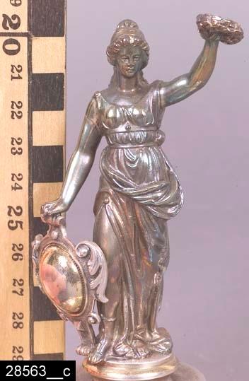 """Anmärkningar: Lock till bägare,  omkring 1884.  Rund nederdel med följande graverade text """"1sta Pris för välskött ladugård af Westmanlands läns Hush. Sällskap 18 28/1 84"""". Ovanför nederdelen finns akantusflikar. Nedanför figuren syns den graverade texten """"SKULTUNA BRUK"""" (bild 28563__b). Längst upp finns en antik kvinnogestalt (möjligen Minerva) med en sköld i högra handen och en segerkrans i den vänstra (bild 28563__c). Möjligen hör invnr. 28563 samman med invnr. 28658. H:135 D:105  Tillstånd: Bägaren saknas. Endast locket finns bevarad.  Historik: Gåva från SAPA AB, Division Service, 2002. Föremålet stod i ett skyddsrum på bruksområdet i Skultuna."""