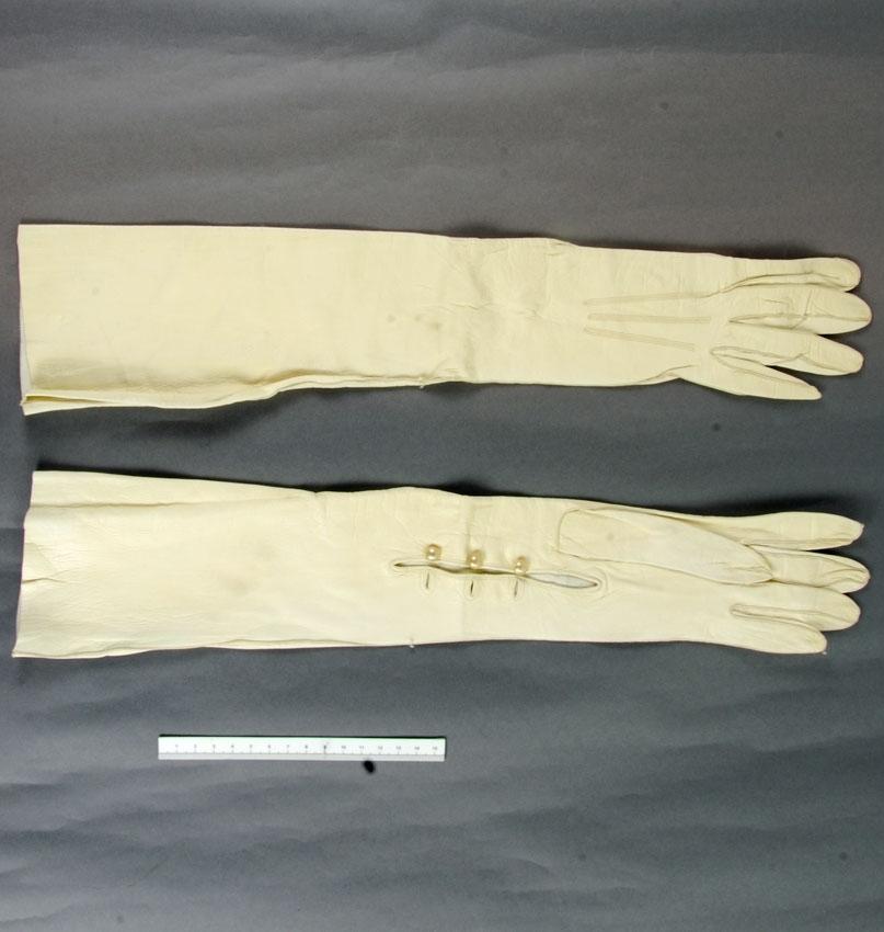 """Anmärkningar: Irsta sn Geddeholm  Handskar, 1 par, vita långa glacéhandskar, av get- eller lammskinn, som når över armbågen. Öppna vid handleden och knäpps där med tre små välvda pärlemoknappar och knapphål. En knapp saknas på ena handsken. Den ena handsken märkt med bläck inuti """"Import 367 29"""", den andra 6 3/4 chevreau garanti."""" dvs kromgarvat getskinn med slät och högglansig yta. (Källa NE)"""