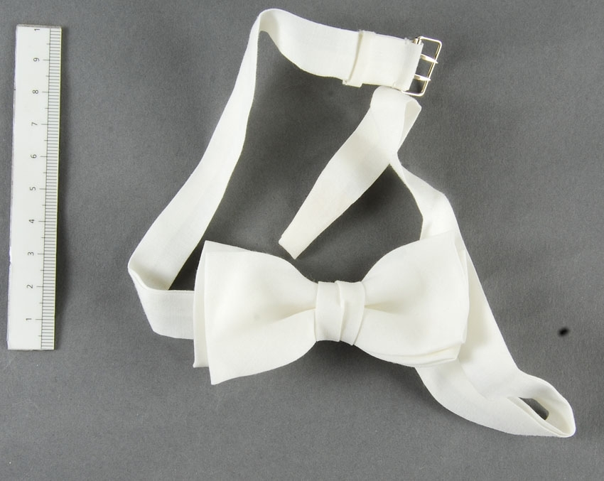 Anmärkningar: Irsta sn Geddeholm  Fluga, 4 st, av vitt bomullstyg knuten i form av en rosett, varav 2 större (Längd 110 mm) av mönstrat vitt tyg varv den ena oanvänd i originalförpackning. Båda de större flugorna försedda med vita band, som knäpps med resår och ring med hake i nacken. De båda mindre flugorna (längd 90 mm) knäpps med sölja och två spetsiga tornen bak i nacken. (Fuga, kläddetalj som har likhet med en fluga, t.ex. en smal halsbindel för herrar, knuten i rosett, eller en liten sydd dekorativ detalj i triangelform Källa NE)