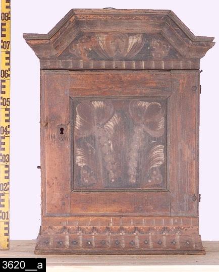 Anmärkningar: Hängskåp, kurbitsmålat, omkring 1800.  Framskjutande brutet krön. Spegelförsedd enkeldörr med gerade och profilerade lister samt en nyckelskylt i järn. Färgen på vänster sida av dörren bär spår av naturligt slitage. En draglåda under dörren. Invändigt en skedhylla samt ett hyllplan. På sidorna finns öglor i järn. på höger sida finns också en järnspik (bild 3620__b). På baksidan finns en upphängningsanordning i järntråd (sannolikt original, bild 3620__c). Svagt kälade sockellister. H:830 Br:650 Dj:355  Måleriet är utfört av en dalmålare. Dalfolkets arbetsvandringar är väl belagda inom forskningen. Man vet också att dalmålarna kunde röra sig på mycket stora ytor, t.o.m. till Norge och Finland. Att de tog sig ned till Västmanland råder det ingen tvekan om.  Tillstånd: Lås och nyckel saknas.  Historik: Inköpt genom Nils Nygren av skroth. Karlsson, Tuna, Svedvi sn, 1925 för 6kr.  Negativnummer X-1690