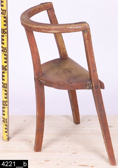 """Anmärkningar: Stol, 1800-tal.  Halvcirkelformat överstycke. Tre konkava ben som löper från marken till överstycket. De främre benen är fästa i överstycket med järnförstärkningar. Rundad träsits. Bilderna 4221__a och b illustrerar samtliga beskrivningar från två vinklar. H:760 Br:570 Dj:345  Hela stolen är rödmålad och bär spår av naturligt slitage.  Historik: Köpt av Emma Kristina Andersson, Svartmuren, Ramnäs sn,  vid N. Nygrens besök för 25 öre, 6. 3. 1925. Enligt liggaren är stolen """"Gjord av Lars Krus""""."""