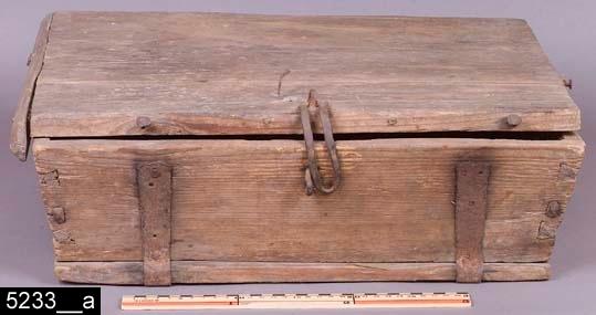 Anmärkningar: Skrin, 1700/1800-tal.  Gångjärnsförsett platt lock med en hasp längst fram som fästs över en järnögla på framsidan. Invändigt är skrinet tomt (bild 5233__b). Samtliga sidor är snedställda (bild 5233__a-c). H:165 Br:505 Dj:390  Tillstånd: Höger list på locket saknas.  Historik: Gåva från fröknarna Ringström, Hedkärra, Västanfors sn.  Negativnummer X-1630
