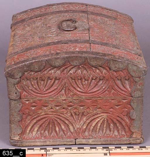 Anmärkningar: Skrin, 1700-tal.  Gångjärnsförsett välvt lock med ett järnhandtag. På framsidan finns en nyckelskylt av järn. Samtliga sidor är rikt försedda med skurna ornament. Hela skrinet är rödmålat och bär spår av naturligt slitage. Den röda färgen är gammal, men ej ursprunglig. Den grå originalfärgen syns igenom på flera ställen. H:160 L:265 Dj:220  Bild 635__b visar närbild på locket. Bild 635__c visar närbild från ena kortsidan. Bild 635__d visar närbild på baksidan.  Tillstånd: Skrinet är låst och går inte att öppna. Nyckel saknas. Skada på lockets framsida.  Historik: Förvärvat från Medåker sn, S. Ryby.
