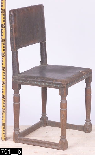 """Anmärkningar: Stol, s.k. åttaslåstol (benämning efter antalet benslåar), senrenässans modell, 1600-tal.  Rakt överstycke och ryggslå samt raka bakstolpar. Mellan ryggstolparna är läder uppspänt. Det är fäst i ryggstolparna, överstycket och ryggslån med tännlikor i mässing. Stoppad sits med läderöverdrag som är fäst i sargarna med tännlikor i mässing. Samtliga sargar är profilerade i nederkanterna. Fyra profilsvarvade ben (bild 701__b). Tre kälade fotslåar. H:935 Br:470 Dj:430  Invnr. 701 är enligt liggaren inköpt som en stol. Invnr. 10447 är enligt liggaren inköpt som två stolar. Någon gång har en förväxling uppstått och invnr. 701 har införts i invnr. 10447. Detta är förståeligt då alla tre stolar är identiska med undantaget att invnr. 701 är helt av ek, de andra är av furu. Alla är av senrenässans typ och dekorerna är identiskt utförda. Högst sannolikt är alla tre stolar utförda av samma snickare. I samband med projektet Access genomgång av bl.a. stolar 2006 har invnr. 10447 splittrats. Se även invnr. 28524.  Tillstånd: Främre fotslån saknas. Den högra fotslån fäster inte i höger bakstolpe. Lädret är slitet.  Historik: I liggaren står det """"Fordom nyttjad vid Snefringe Häradsrätt."""" Gåva av A.Larsson, Björunda, Munktorp sn.  Negativnummer X-2202"""