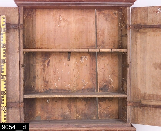 """Anmärkningar: Dubbelskåp på fotställ, rödmålade. Delarna hör ursprungligen ej samman. Fotstället är från mitten av 1700-talet, medan dubbelskåpet är tillverkat under 1800-talets första hälft, dock kan vissa delar av det senare vara av äldre datum.  Dubbelskåp: Framskjutande krön. Under krönet finns initialerna """"C J A"""" (vänster dörr) och årtalet """"1839"""" (höger dörr) (bild 9054__b). Spegelförsedda pardörrar med gerade och profilerade lister. Båda dörrar har mässingsnyckelskyltar i rokokostil (bild 9054__c). Den högra dörren har en draganordning i järn (bild 9054__c). På båda sidor finns spiralvridna handtag i järn (bild 9054__g). Sidorna, dörrarna och botten är av ek, bakstycket av furu. Invändigt två hyllplan samt plats för skedar på det översta hyllplanet (bild 9054__e). Spår av tidigare hyllinredning finns (bild 9054__e). Lås i järn på höger dörr. Hank i järn på vänster dörr samt tillhörande hankfäste på det övre hyllplanet. H:845 B:800 Dj:350.  Fotställ: Framskjutande något kälade lister ovanför draglådan. Draglåda med gerade och profilerade lister. Tre beslag i mässing (bild 9054__f), varav det mittersta i rokokostil. Beslagen på sidorna har senbarocka drag. Profilerad list under draglådan. Fyra svängda fötter. H:390 B:825 Dj:370.  Tillstånd: List lös runt högra spegeln (bild 9054__h). Senare draganordning i järn på högra dörren. List saknas på vänster sida på fotstället. Låset på fotstället är löst och ligger i lådan (bild 9054__h), nyckel saknas.  Historik: Gåva av Dr Gustaf Holm, Västerås, 1934.  Negativnummer X-112"""