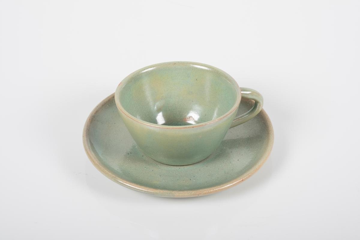 Kopp med skål i keramikk med grønn lasur. Buet hank på koppen. To små knotter (mangler en tredje knott) på undersiden av koppen, usikker funksjon. Skålen er blank på oversiden og matt på undersiden.
