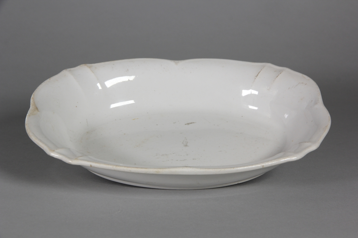 Uppläggningsfat, ovalt av vitt porslin med ojämn kant.