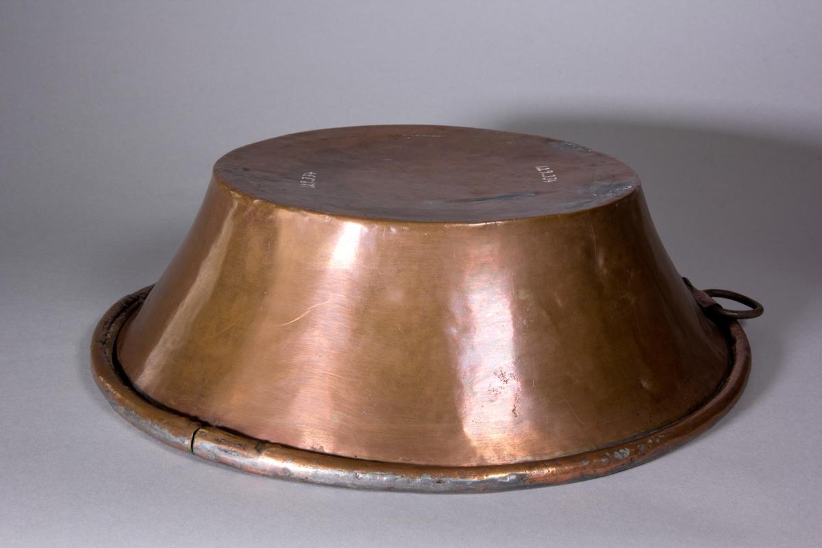 Bunke, rund, av koppar med lätt utställda sidor och smal vulst. Invändigt förtent. Järnring för upphängning.