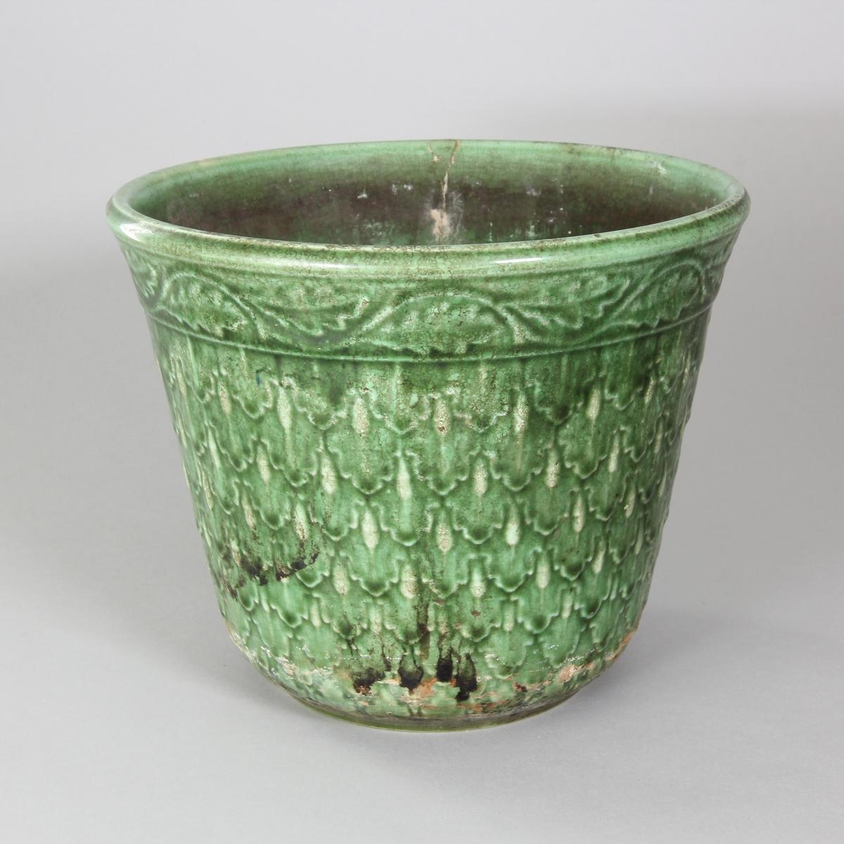 Blomkruka av lergods, grönglaserad in och utvändigt. Mönster av tätt sittande ekollon samt ekblad vid mynningskanten.