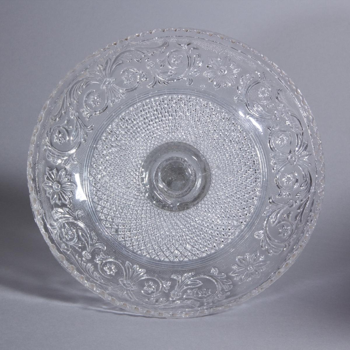 Kakfat av pressat glas. Sexkantig fot, profilerat ben och rund skål med pressat mönster av rankor och rutor samt vågig kant.
