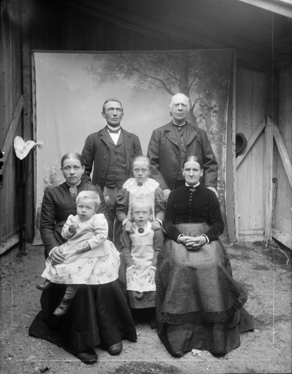 Antatt familiebilde med 7 personer og tre generasjoner med ektefeller. Antatt to besteforeldre, to foreldre og tre døtre på ca 2 til 6 år. Atelierfoto (provisorisk ved reisverksbygning) fra Gudbrandsdalene eller sidedalene i tidsrommet 1890-97