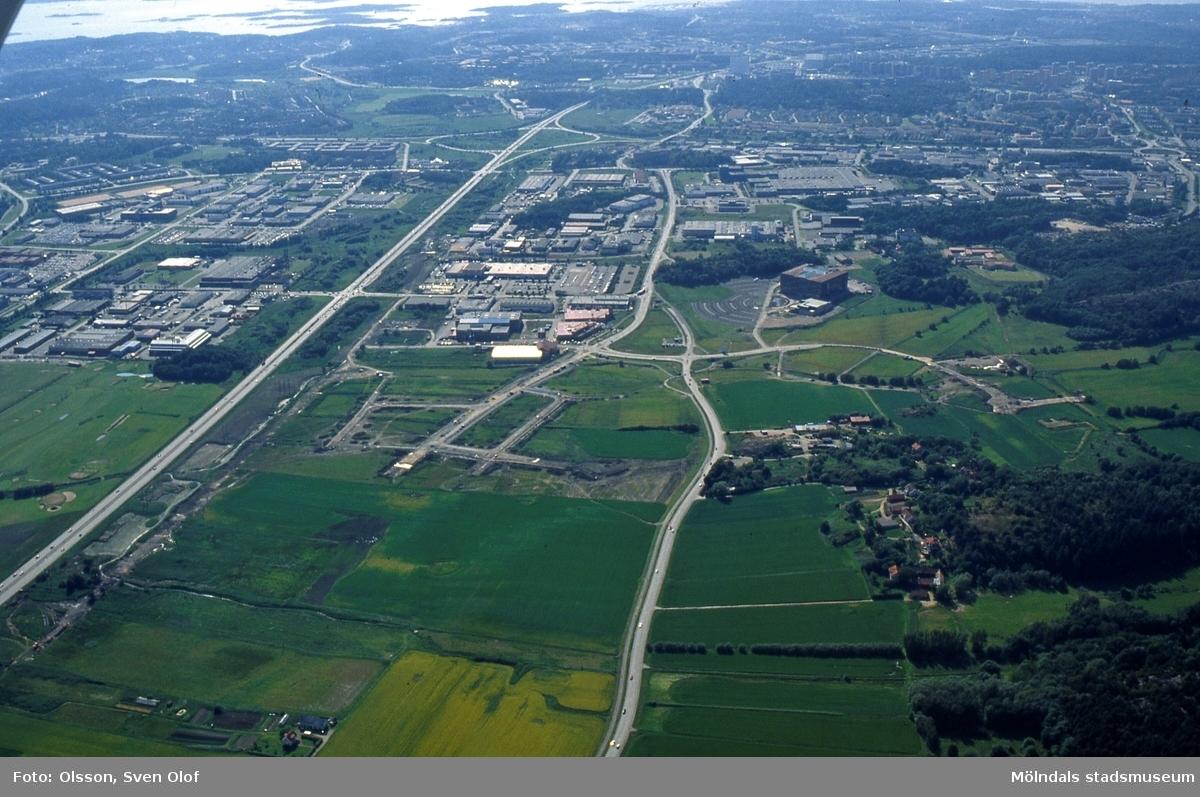 Flygfotografi över del av Mölndal och Göteborg den 4/7 1991. Till höger ses Eklanda och Europahuset. Vägar till industriområdet är utlagda. Till vänster ses Sisjöns industriområde och i mitten Högsbo industriområde.
