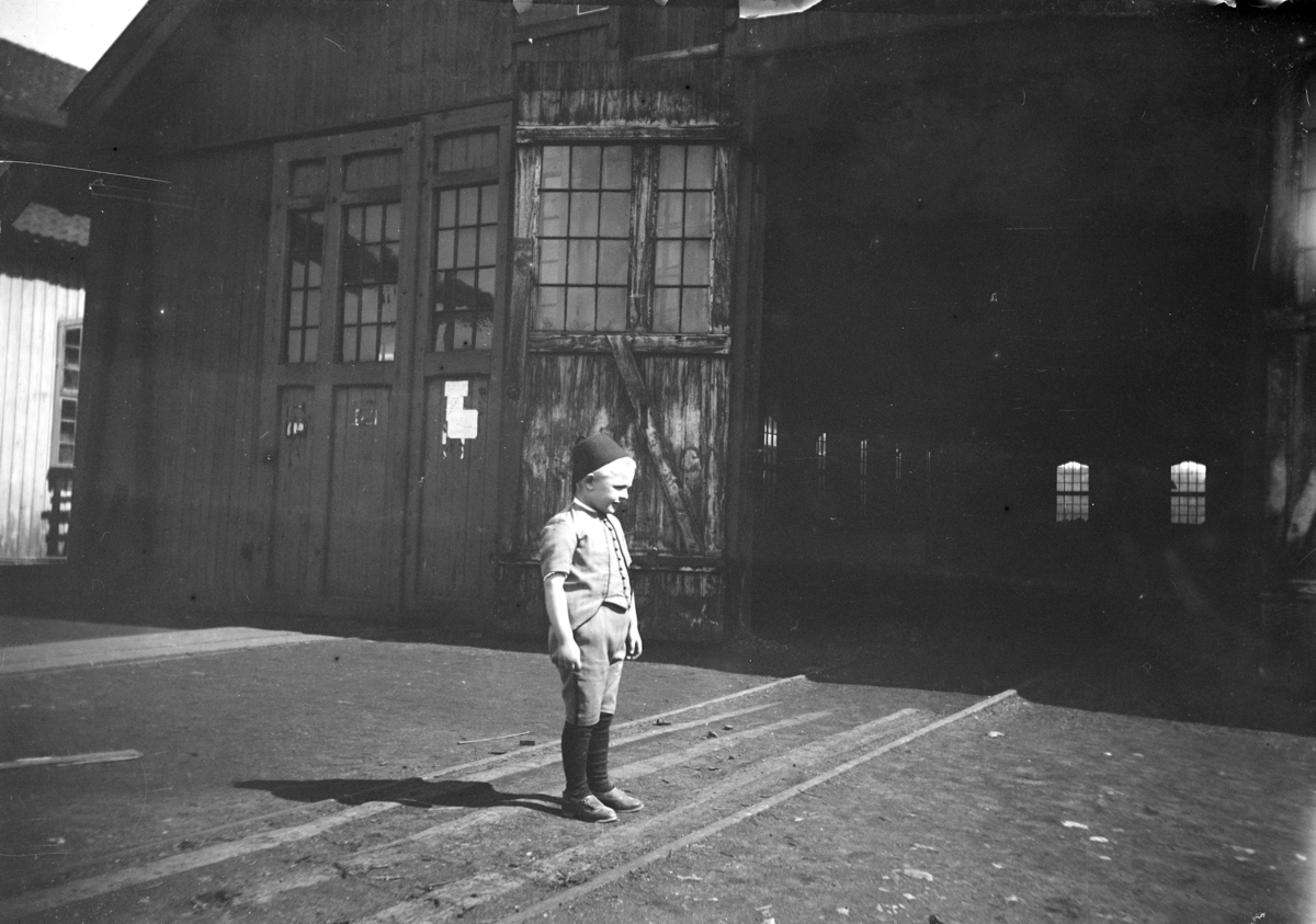 Ukjent gutt, barn, foran industribygning. (Skabo Vognfabrikk?)
