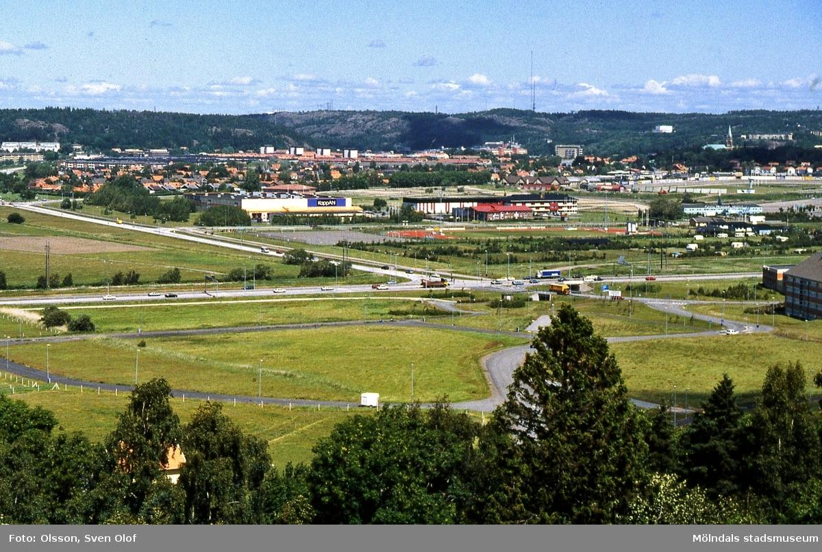 Del av Fässbergsdalen, Mölndal, i maj 1994. Vy från Balltorp över Söderleden och Bifrostgatan mot Kapp-Ahl, idrottsplatsen, campingplatsen samt längst till höger Åby travbana. FD 6:36.