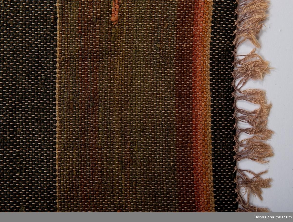 Matta, ensidig, med varp av brunfärgad  bomull och med inslag av växtfärgat ullgarn. Breda ränder av omväxlande gröna, röda, svarta samt  smala gula ränder. På varje färgfält två inplock i  avvikande färg. Bred bård utmed vardera långsidan av melerat garn i brunt och gult. Blekt framsida, i övrigt i mycket gott skick.  Trasmattan kommer från ett dödsbo efter skepparfamiljen Arvid Olsson (f. 1861) och Sofia Charlotta f. Carlsson (f. 1860) och deras ogifta döttrar Alvina Charlotta  (1888-1979), Edith Josefina  (1894-1971), Annie Leontina (1899-1965), Teresia (1887-1972), Mabel samt tre söner i Berglid på Hermanö.  Mattan kan vara vävd av modern eller döttrarna.   Arvid vaskade guld i Kalifornien som ung. han hade tomt i San Fransisco och ville bygga där. Sofia Charlotta vill inte lämna Gullholmen, så den blivande maken kom hem.  Kerstin Lychou tittade på mattan i samband med sin  slöjdinventering på 1980-talet.  Litt: Lychou, K.: Folkkonst i Bohuslän, Warne förlag 1996, s. 104 ff.