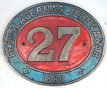 Oval skylt av mässing med text i relief mot röd- och blåmålad botten. Från ångloket BJ K 27. Loket såldes till en skrothandlare 1947 som i sin tur sålde loket till SJ 1948, 1956 kom loket till Sveriges Järnvägsmuseum. Beyer Peacock & Co. Nº 1933.
