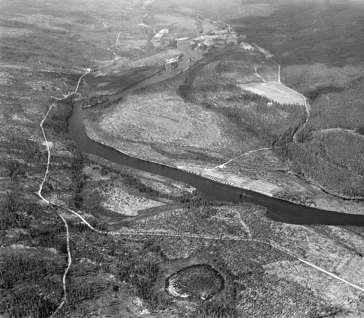 Flyfoto av tømmerterminalen på Kroken ved Femundselva (Trysilelva) i Engerdal.  Fotografiet ble tatt i midten av mai 1986, fra en posisjon i lufta med kameraet vendt nedover og nordover.  Den nevnte terminal- eller velteplassen skimtes ved østre elvebredd.  Den hadde adkomstveg fra fylkesveg 581 (strekningen mellom Sundet i Engerdal og Engerneset i Trysil), like ved Fiskvikkrokbekkens utløp i hovedvassdraget (her ved høyre bildekant).   Da dette fotografiet ble tatt lå det 5 000 kubikkmeter massevirke på denne plassen.  Bygginga av terminalplasser i Trysil og Engerdal ble mulig etter at det var bygd skogsbilveger som overflødiggjorde tømmerfløtinga i mange av de minste sidevassdragene.  Det var i 1965 at styret i Klarälvens Flottningsförening, i samråd med Trysilvassdragets skogeierforening, vedtok å bygge slike terminalplasser.  Her ble tømmeret handtert med digre griplastere, og i åra som fulgte ble det også investert i barkemaskiner, som overflødiggjorde mye av det tunge arbeidet med barkespader på hogstfeltene vinterstid. Den ringformete forsenkningen i terrenget sentralt i forgrunnen kalles Kroktjønna eller Rankviktjønna.
