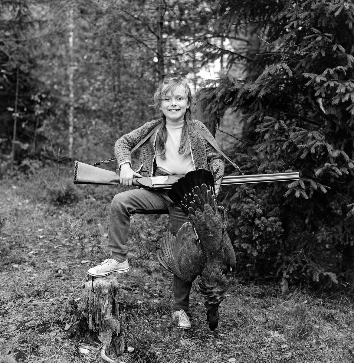 Glad jente med haglegevær og nyskutt tiur.  Fotografiet er tatt i et skogsterreng der jente står med den ene foten på en gammel stubbe, med våpenet i ei reim bak nakken og løpet pekende mot sida.  Hun holder tiuren etter beina i venstre hånd, slik at hodet peker mot bakken, vingene til sidene og halen til værs.  Fotografiet er tatt av jegeren og fotografen Kjell Søgård, og det var trolig han som eide våpenet og som hadde skutt fuglen.  Jenta er dattera, Vera Søgård, seinere Vera Søgård Bryn.  Fotografiet er tatt i 1969. Storfugljakt.