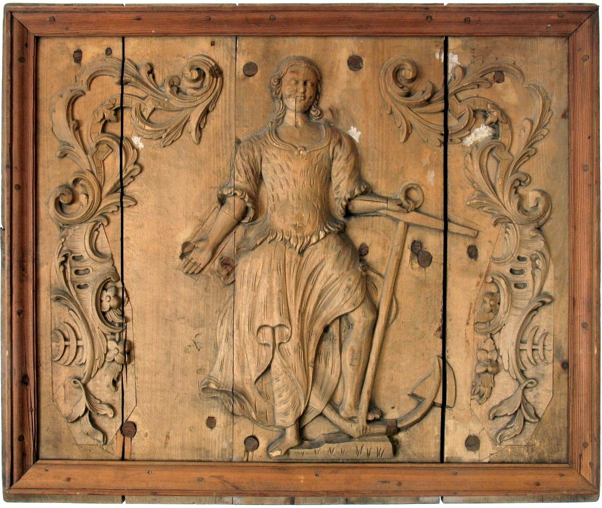 Stående kvinneskikkelse som holder et oppreist  anker i sin venstre hånd. Flankert av løv og knekkede bånd i régence, blomster og rokokkoornamenter.