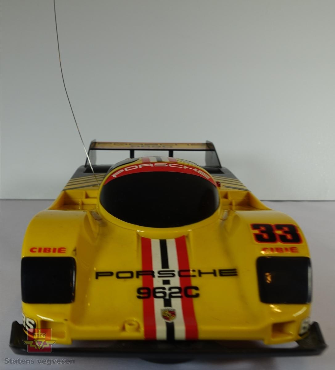 Miniatyr, lekebil i eske. Laget av papp med en slags neon lilla farge. Bilen er nesten helt gul utenom de svarte stripene på bakenden av bilen, kan minne deg om en bie. Skala. 1:12